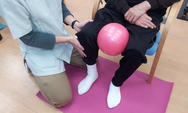 その方に合った訓練方法で個別に指導 介助しています。写真はボールを使い下半身の筋肉強化をしています。